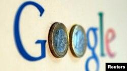 FILE - An illustration picture shows a Google logo with two one Euro coins, taken in Munich.