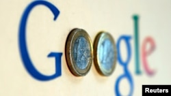 FILE - An illustration picture shows a Google logo with two one Euro coins.