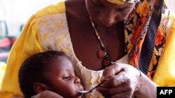 母亲在世界粮食计划署资助的中心给孩子喂食