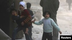 Children walk at a site hit by what activists said was a barrel bomb dropped by forces loyal to Syria's President Bashar al-Assad in Aleppo. (March 6, 2014.)