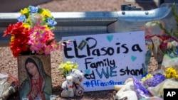 """Unas flores y una imagen de la Virgen de Guadalupe adornan un monumento conmemorativo improvisado en honor de las víctimas de un tiroteo en un centro comercial en El Paso, Texas, el domingo 4 de agosto de 2019. El letrero dice: """"El Paso es una familia. Permanecemos unidos""""."""