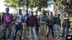In this Aug. 28, 2014, photo an Anti-Balaka group that defends the Christian neighborhood near the Church of the city stands for a photo in Boda, Central African Republic. More than 5,000 people have died in sectarian violence in the Central African Republic since December, according to an Associated Press tally. (AP Photo/Sylvain Cherkaoui)