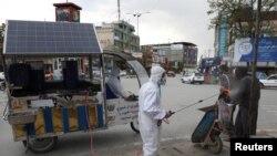 在阿富汗首都喀布爾,工作人員正在向一名男子身上噴灑消毒劑(2020年4月19日)。