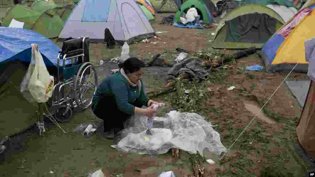 Une femme lave ses vêtements dans un camp où des milliers de réfugiés attendent d'être autorisés à franchir la frontière, le 4 mars 2016.