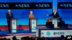 Martin O'Malley, right, speaks alongside Bernie Sanders, left, and Hillary Clinton, center, during a Democratic presidential primary debate at Saint Anselm College in Manchester, N.H., Dec. 19, 2015.