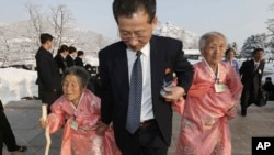 FILE - A North Korean man escorts his relatives as they reunite with their South Korean family members at Diamond Mountain resort in North Korea, Feb. 21, 2014.