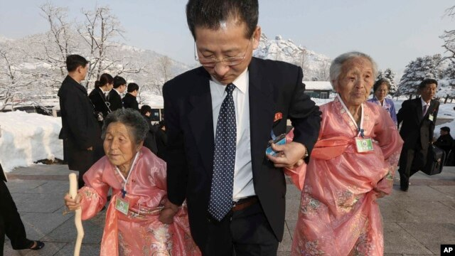 A North Korean man escorts his relatives as they reunite with their South Korean family members during the Separated Family Reunion Meeting at Diamond Mountain resort in North Korea, Feb. 21, 2014.