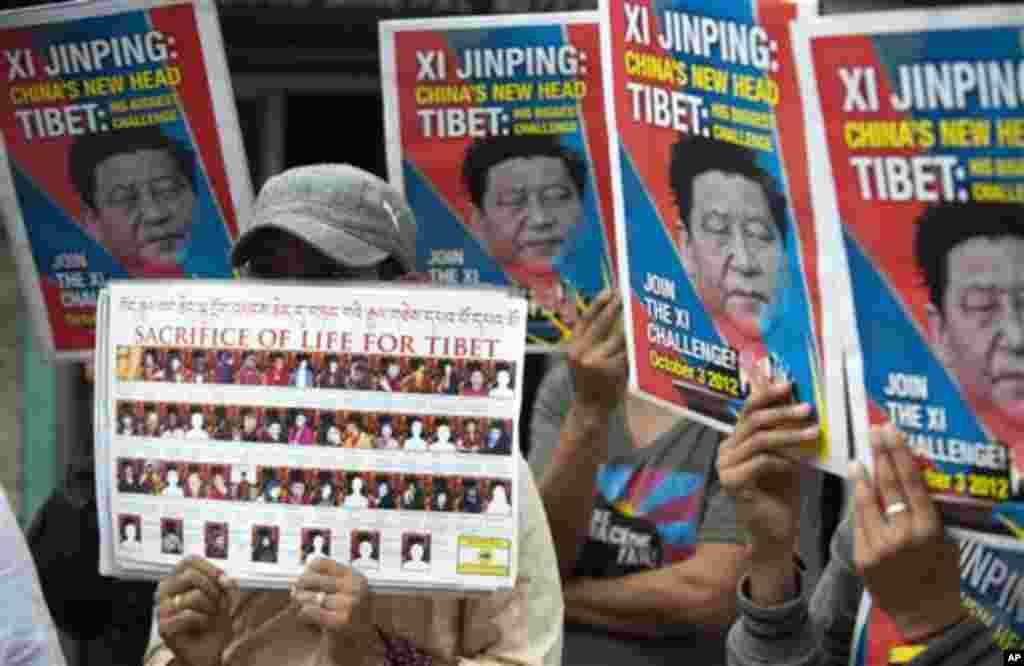 ພວກຊາວທິເບດພັດຖິ່ນ ທີ່ເມືອງທໍາມະສາລາ ຂອງອິນເດຍ ພາກັນຍົກຮູບຂອງທ່ານ Xi Jinping ຊຶ່ງໃນຂະນະນັ້ນ ກໍາລັງຈະເປັນຜູ້ ກໍາຕໍາແໜ່ງຜູ້ນໍາສູງສຸດຂອງຈີນ ຂຶ້ນ ເພື່ອຮຽກຮ້ອງໃຫ້ແກ້ໄຂວິກິດການ ໃນທິເບດ ໃນວັນພຸດ ທີ 3 ຕຸລາ 2012. (AP Photo/ Ashwini Bhatia)