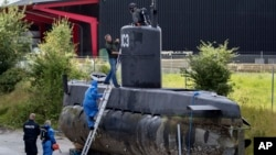 FILE - Police technicians board Peter Madsen's submarine UC3 Nautilus, Aug. 13, 2017, on a pier in Copenhagen harbor, Denmark. A Danish prosecutor said Tuesday Jan. 16, 2018 that inventor Peter Madsen has been charged with murdering Swedish journalist Kim Wall during a trip on his private submarine.