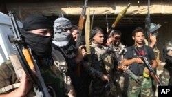 Iraqi Shi'ite Turkmen gunmen gather as they prepare to patrol around the village of Taza Khormato in the northern oil rich province of Kirkuk, June 20, 2014.