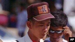 A Cambodian vendor wearing many kinds of glasses on his front shirt, cleans a sun glasses to sell in the Olympic stadium.