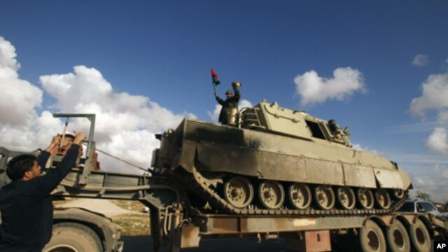 A rebel stands atop a destroyed tank, belonging to forces loyal to Libyan leader Muammar Gaddafi, after a coalition air strike, along a road between Benghazi and Ajdabiyah, March 21, 2011