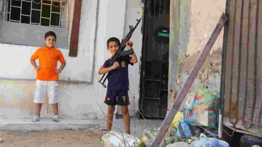 پسربچه در طرابلس با تفنگ يک رزمنده در حال بازی است. تفنگ خالی است.