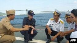 Thiếu tá Hải quân Nguyễn Thái Sơn và Thiếu tá Caroline Adler giải thích chức năng của bề mặt chống trượt được sử dụng trên boong tàu Hải quân Hoa Kỳ trong buổi huấn luyện về bảo trì trên tàu khu trục USS Chung-Hoon tại Đà Nẵng, Việt Nam (hình chụp ngày 17/7/2011).