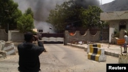 A man takes a photo of smoke rising from the site of an attack on the Political Security Agency building, the headquarters of the Yemeni intelligence services in the southern provinces, in the southern Yemeni city of Aden August 18, 2012.