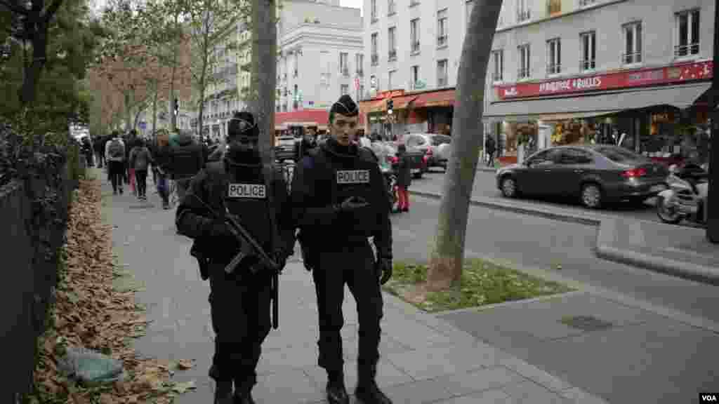 Polisi berpatroli dekat sebuah memorial di luar gedung konser Bataclan sehari setelah serangan teror di Paris (14/11).