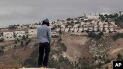 یکی از ساکنان «معاله آدومیم» در حال نگاه کردن به این بزرگترین شهرک یهودی نشین اسرائیلی واقع در کرانه باختری - ۵ دسامبر ۲۰۱۲