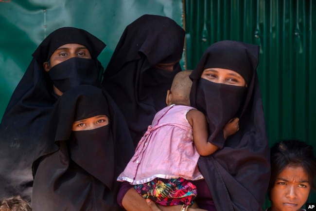Rohingya Muslim women along with their children, who have crossed over from Myanmar into Bangladesh, wait for the arrival of Queen Rania of Jordan, at Kutupalong refugee camp in Bangladesh, Oct. 23, 2017.