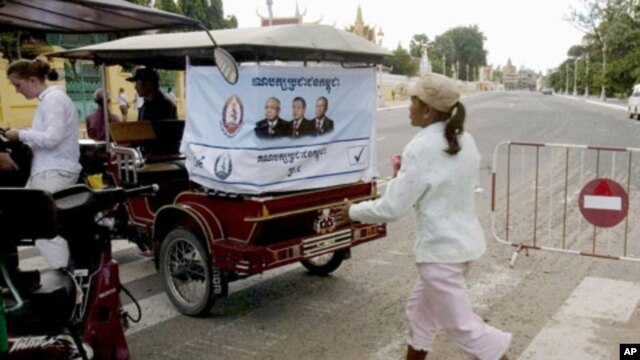An election campaign poster of Prime Minister Hun Sen's ruling Cambodian People's Party hangs on the back of a motorized rickshaw parked at a blocked street in front of the Royal Palace in Phnom Penh.