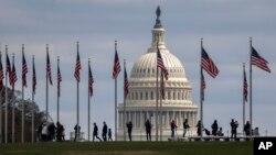 Người dân đi lại giữa các lá cờ Mỹ với hình ảnh Quốc hội Mỹ ở phía sau trong bức ảnh chụp hôm 15/3. Các thành viên đảng Dân chủ và đảng Cộng hoà bắt đầu tranh cãi về một gói cứu trợ mới nhằm hỗ trợ tài chính trong dịp bùng phát dịch virus corona.