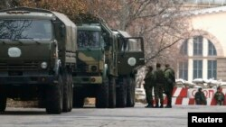 Armed personnel and military trucks without markings are seen near a checkpoint on territory controlled by the self-proclaimed Donetsk People's Republic in Donetsk, eastern Ukraine, Nov. 12, 2014.