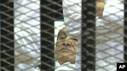 This video image taken from Egyptian State Television showing former Egyptian president Hosni Mubarak laying on a hospital bed flanked by his two sons Gamal and Alaa, inside a cage of mesh and iron bars in a Cairo courtroom, Wednesday Aug. 3, 2011, as hi