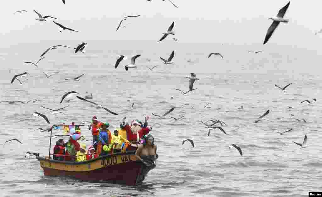 Ruben Torres, dressed in a Santa Claus outfit, waves to people from a boat with fishermen on Christmas Eve, along the coast of Valparaiso city, about 121 km (75 miles) northwest of Santiago, Chile.