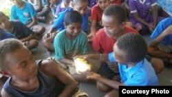 Des élevés manipulent une lampe solaire lors d'une leçon sur les énergies renouvelables.