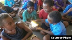 In a remote village in Fiji, children get a chance to learn about renewable energy as part of their curriculum and try out a new solar powered lamp donated to the school. (Energy for All)