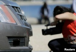 FILE - A member of the media photographs the front-end sensors of a 2011 Cadillac SRX autonomous car created by students and staff of Carnegie Mellon University, June 24, 2014, in Washington.