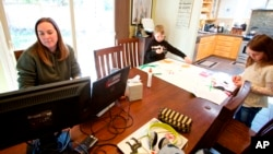 In this March 17, 2020 photo from Beaverton, Oregon, Kim Borton works from home while her children Logan, center, age 6 and Katie, age 7, as they work on an art project.
