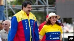 Venezuela's President Nicolas Maduro and first lady Cilia Flores jump during the closing campaign rally in Caracas, Venezuela, Dec. 3, 2015.