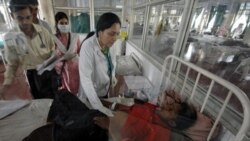 A doctor attends to a hepatitis patient in a special isolation area at a hospital in Ahmadabad, India