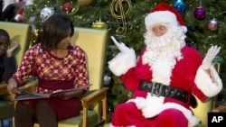 Santa Claus gestures toward first lady Michelle Obama, at Children's National Medical Center in Washington
