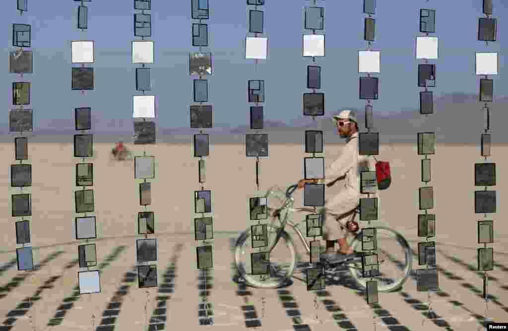"""مردی در حال عبور از کنار یک اثر هنری نصب شده در جریان فستیوال هنری موسوم به """"کارناوال آیینه ها"""" در منطقه موسوم به صحرای """"تخته سنگ سیاه"""" در ایالت نوادا، غرب ایالات متحده - ۹ شهریور ۱۳۹۴"""