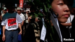 """一名身穿印有天安门""""坦克人""""文化衫的抗议者走在约有数百人的游行队伍中。6月1日,香港举行了数千人的游行活动,以纪念""""六四""""25周年"""