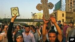 Wata Musulma ta taga Alkura'ani mai girma a lokacin da ita shiga zanga zangar goyon bayan yan uwantaka ga zanga zangar da Kiristoci yan darikar Coptic suka yi.