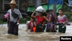People wade through a flooded street in Bago, Myanmar, July 27, 2018.