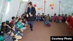 Lilah Salih, a Yazidi woman from a village outside Sinjar in northern Iraq, resettled in the U.S. with her husband in 2017. She is pictured here working Yazidi children when she was in the Sharia refugee camp after the attack on Sinjar.