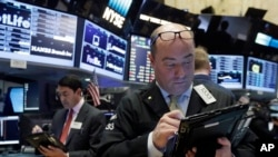 FILE - Trader Christopher Morie, right, works on the floor of the New York Stock Exchange.