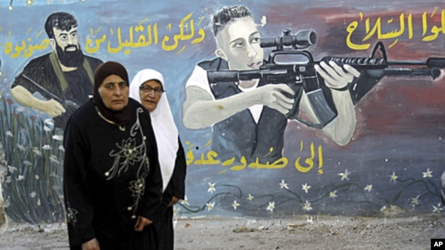 Palestinian women walk next to a mural of militants on the first day of Eid al-Fitr in the West Bank town of Jenin, August, 30, 2011.