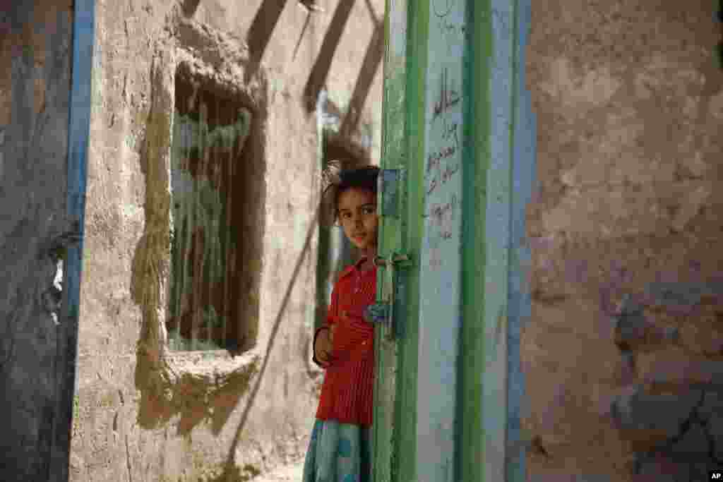 A girl stands in a doorway as she watches children receiving a polio vaccination, during a house-to-house polio immunization campaign in Sana'a, Yemen.