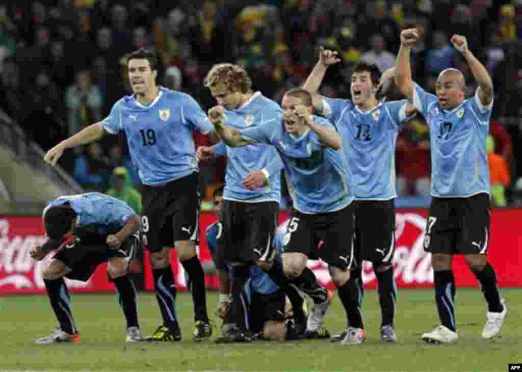 Команда Уругвая радуется пенальти, забитому в ворота Ганы. Уругвай достиг полуфинала Кубка мира впервые с 1970 года, победив Гану со счетом 4:2. (Фото АП / Bernat Armangue)