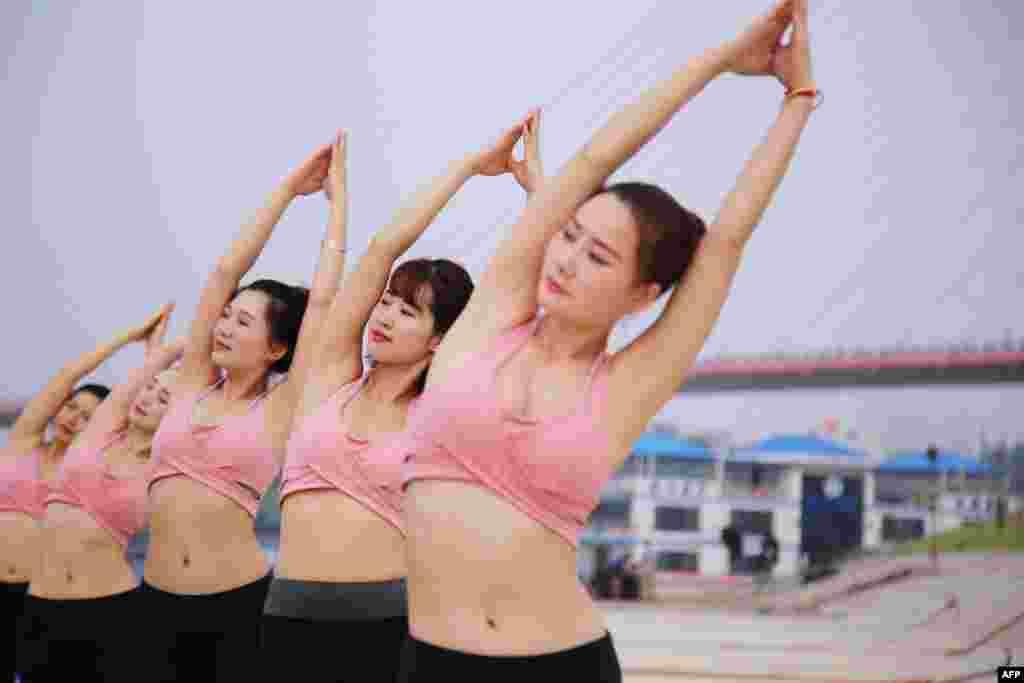 """2018年6月21日,中国湖北省的十堰举办国际瑜伽日,人们参加瑜伽课程。在中国, 由于对瑜伽的推广大多以""""美体健身""""为卖点,女性成为中国瑜伽爱好者中的压倒性多数。很多男性认为,瑜伽的动作不够阳刚,甚至有些男性以为,瑜伽就是专门为女性锻炼身体而诞生的。"""