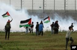 Izraelski vojnici bacaju suzavac na palestinske demonstrante na pojasu Gaze, 30. marta 2019.