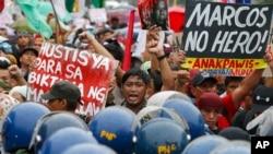 Para pemrotes memegang plakat saat melakukan aksi demo di dekat gerbang Taman Makam Pahlawan di kota pinggiran Taguig, sebelah timur Manila, Filipina, untuk memprotes demonstrasi massal dan perayaan HUT ke-100 mendiang diktator Filipina Ferdinand Marcos, Senin, 11 September 2017.