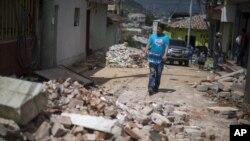 Seorang warga membawa satu galon air melewati jalan yang dipenuhi puing-puing bangunan yang roboh akibat gempa di San Pedro, Guatemala (7/7). (AP/Luis Soto)