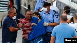 Un inmigrante llora al llegar a Malta mientras carga su hijo tras ser rescatado.