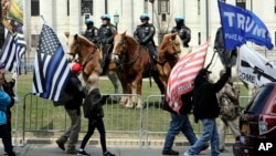 Members of the Albany police department mounted unit offer a police presence as gun rights activists with the National Constitutional Coalition of Patriotic Americans take part in a national rally aimed at pushing back against calls for stronger gun control measures outside the state Capitol, April 14, 2018, in Albany, New York.