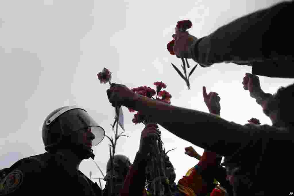 People offer flowers to a civil guard at the entrance of a sports center, assigned to be a referendum polling station by the Catalan government in Sant Julia de Ramis, near Girona, Oct. 1, 2017.